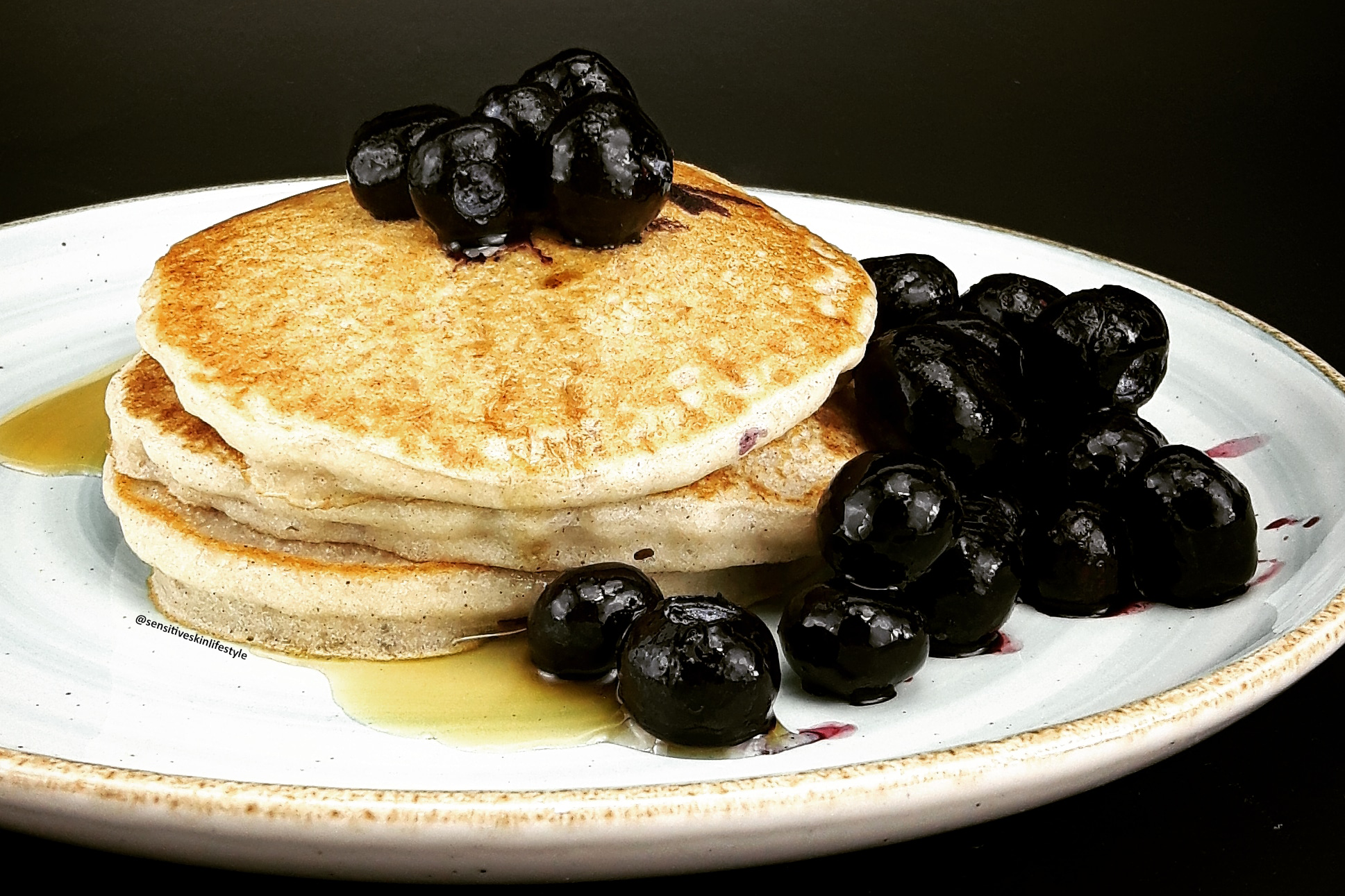 Side view photo of Catherine's home-made buckwheat pancakes with maple syrup and blueberries